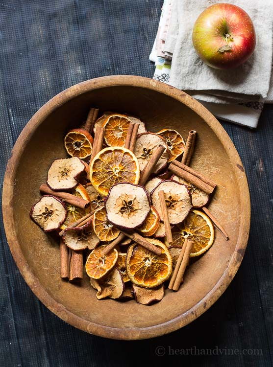 Homemade potpourri made with natural apples, orange slices and cinnamon sticks in a wooden bowl.