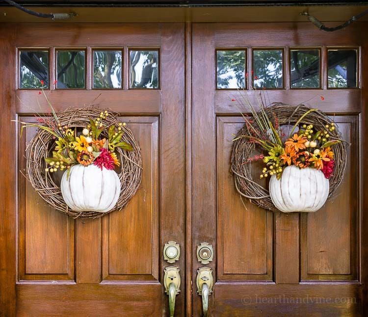 A floral pumpkin wreath on front doors.