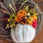 A pumpkin wreath made with half a pumpkin that acts as a vase for faux flowers is a great way to add beautiful fall color to your front door.