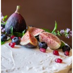Partial section of the top of a cake with figs, berries and pomegranate seeds.