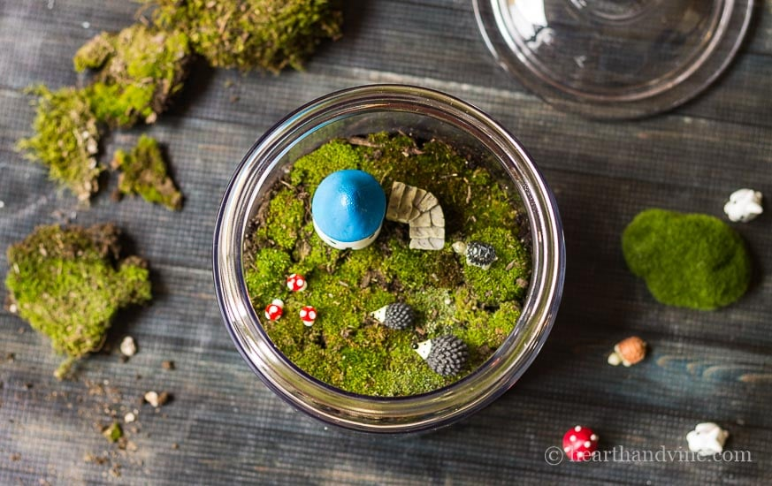 Fairy garden accessories in glass jar.