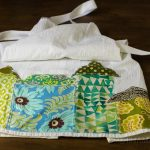 Tea towel aprons are super simple to make. This one is decorated with whimsical fabric houses appliqued at the bottom for a fun look.