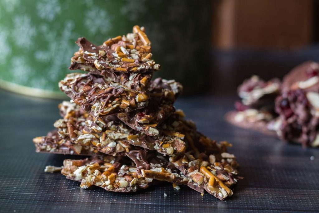 Chocolate bark candy with pretzels and pecans stacked.