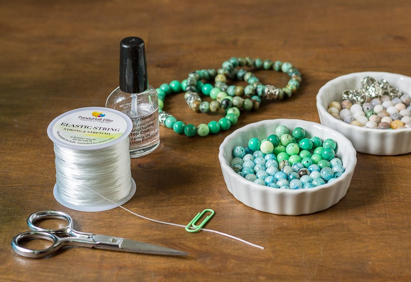 Healing stone bracelet supplies, elastic thread, stones, scissors, a paperclip and clear nail polish.