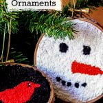 A snowman face punch needle ornament, and a cardinal bird on a branch hoop ornaments.
