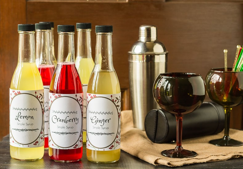 Simple syrups bottles in lemon, cranberry and ginger next to some barware and accessories.