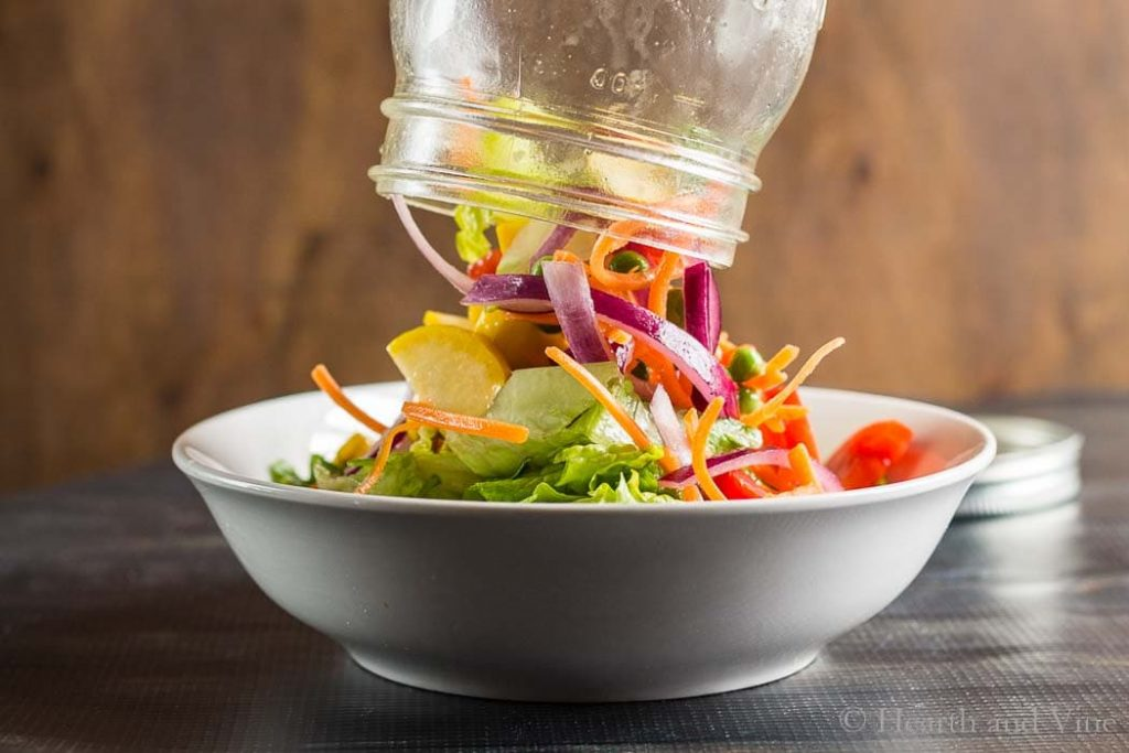 Pouring rainbow jar salad into bowl.