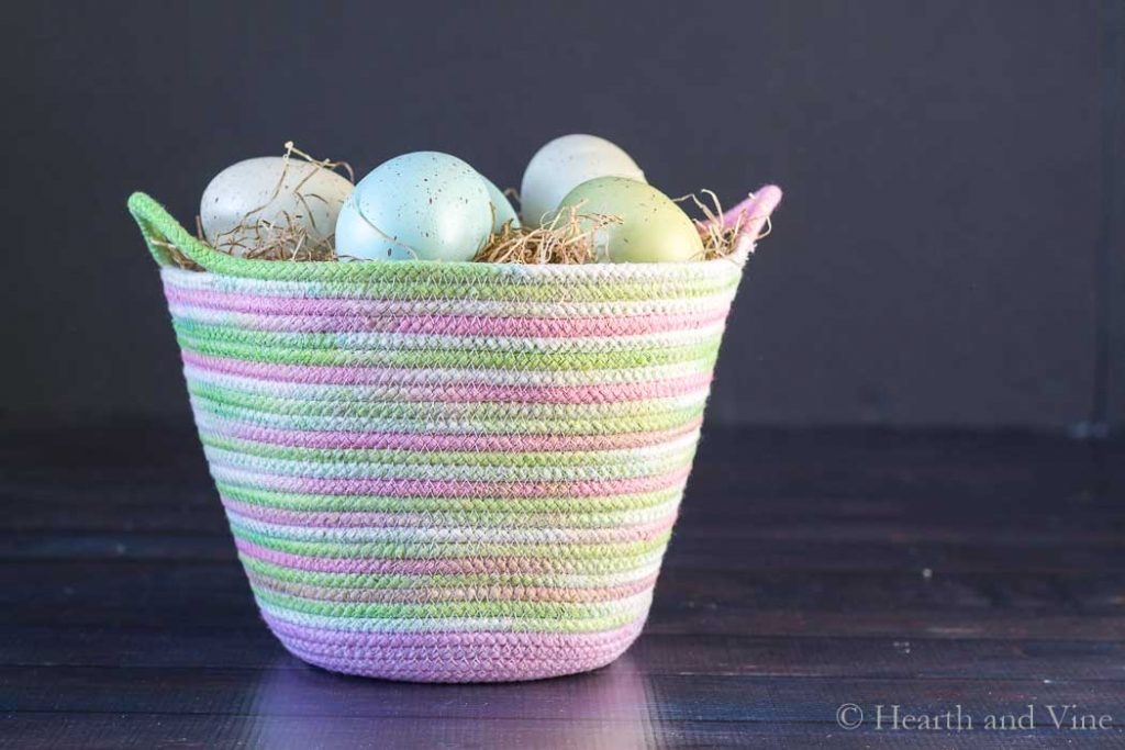 Dyed rope basket with colored eggs.