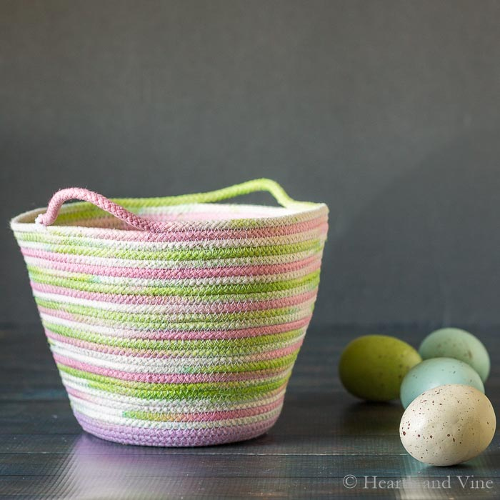 Dyed rope basket for Easter next to eggs.