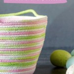 Pink, green, white and lavender rope basket next to faux Easter eggs.