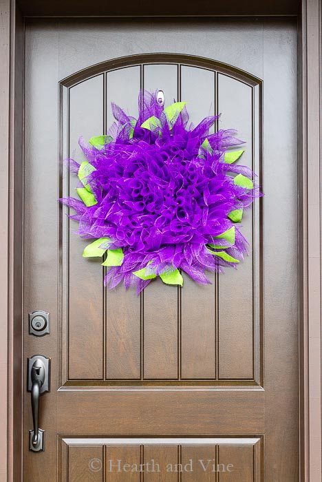 This dahlia deco mesh wreath is super easy to create, and it a perfect bright and cheerful way to decorate you front door for the summer.