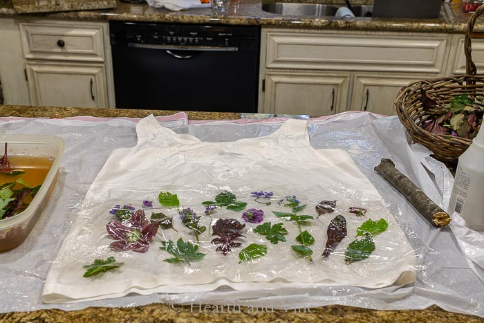 Silk blouse with plant material covered in plastic wrap.