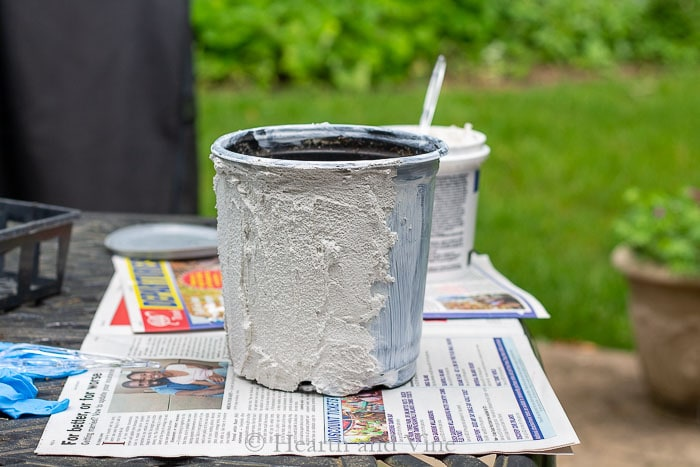 Spreading grout on plastic pot.
