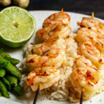 Plate with two skewers of grilled shrimp on rice with a lime and peas.