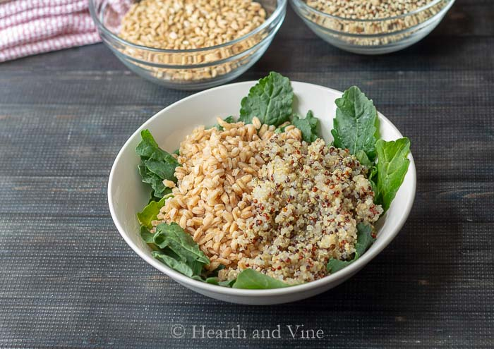 Cooked farro, quinoa and raw baby kale.