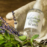 Spray bottle of floral water next to fresh mint and lavender.