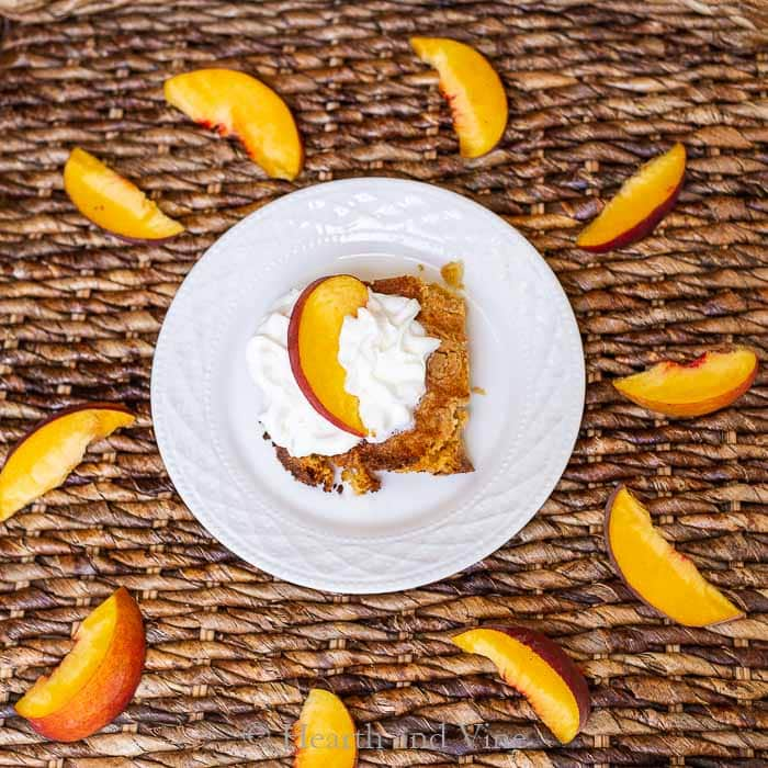 Aerial view of fresh peach dump cake serving with cream and peach slice.