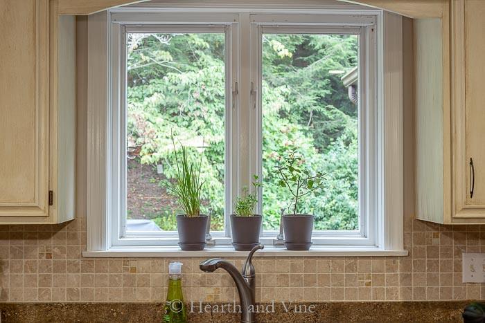 Three pots with herbs on kitchen windowsill