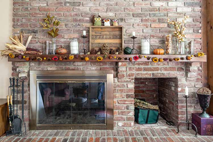 Family room mantel decorated for fall with dried flower garland