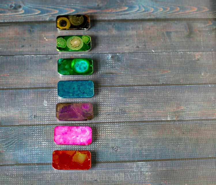 Seven tins decorated with alcohol inks