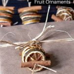 Brown paper package with raffia and a sliced dried fruit stacked ornament tied on top.