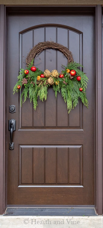 Winter wreath on front door with fresh and faux materials