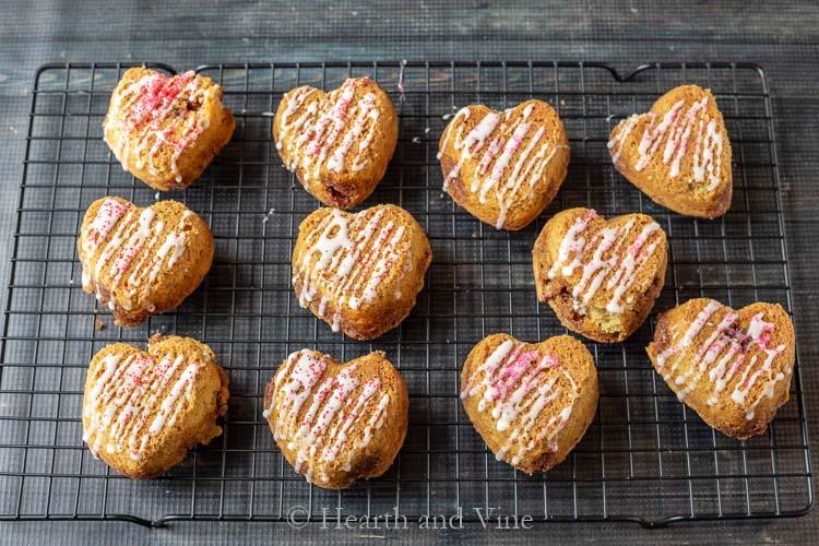 Mini heart cinnamon roll cakes on rack with glaze
