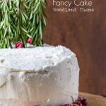 White layer cake with sugared cranberry and rosemary stems for trees.