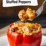 Red bell pepper filled with chicken, rice, beans and cheese. A forkful is lifted above.