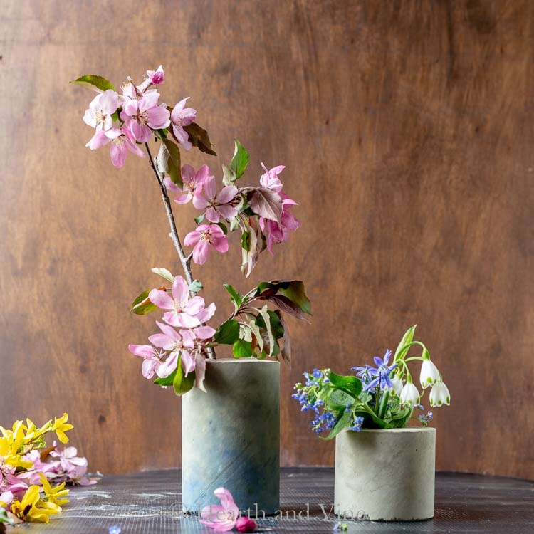 Two concrete vases with flowers inside