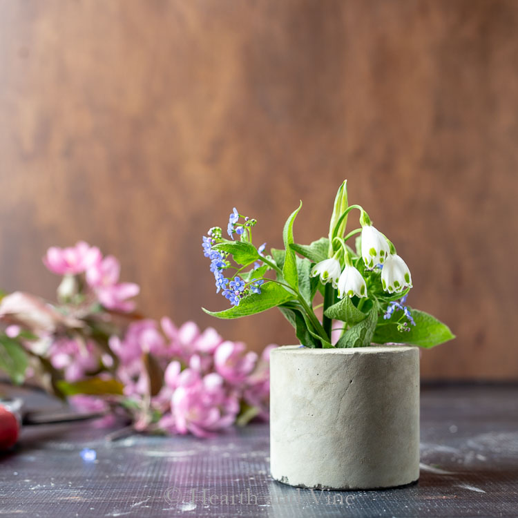 Small concrete vase with blue and white flowers