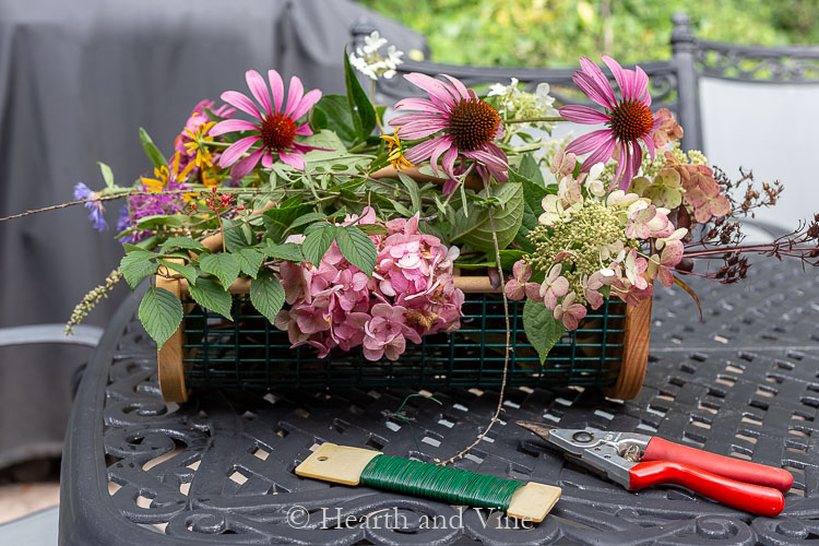 Basket of flower material and pruners and floral wire.