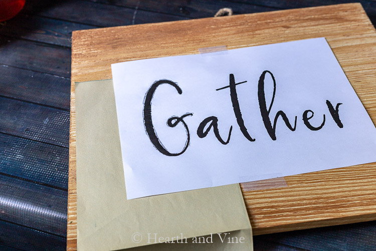 Tracing the word Gather on wood sign