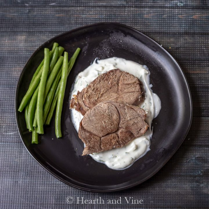Sliced slow cooker leg of lamb with tzatiki sauce and green beans