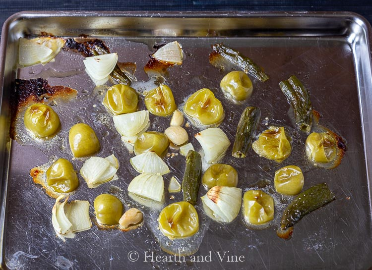Tomatillos, onion, peppers and garlic on cookie sheet after roasting