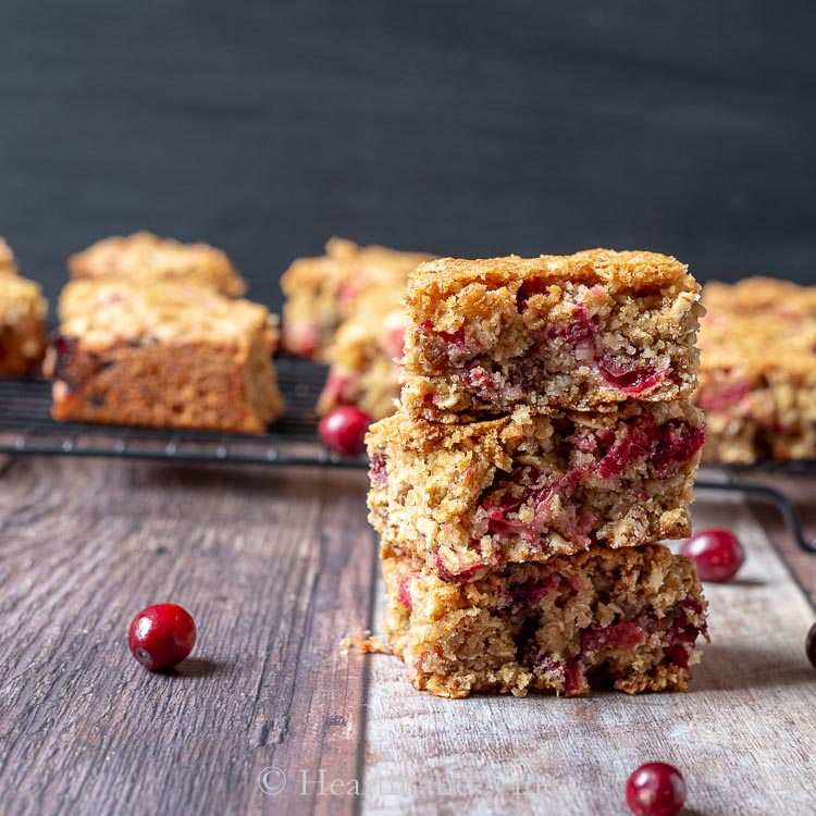 Stack of three cranberry oatmeal bars and scattered fresh cranberries