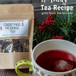 Bag of Christmas morning tea blend next to a floral teacup with red tea and mesh teaball.