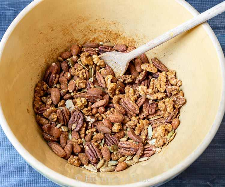 Mixing roasted nuts with spices in a large bowl