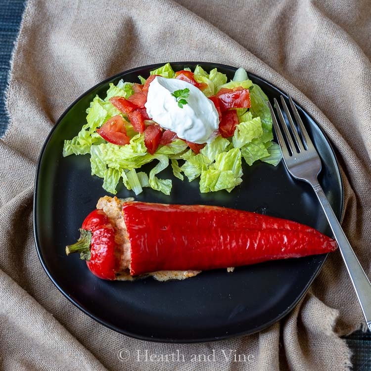 Plate of stuffed Carmen pepper with lettuce tomatoes and sour cream