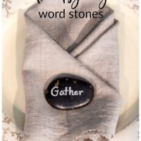 Thanksgiving word stone on linen napkin place setting