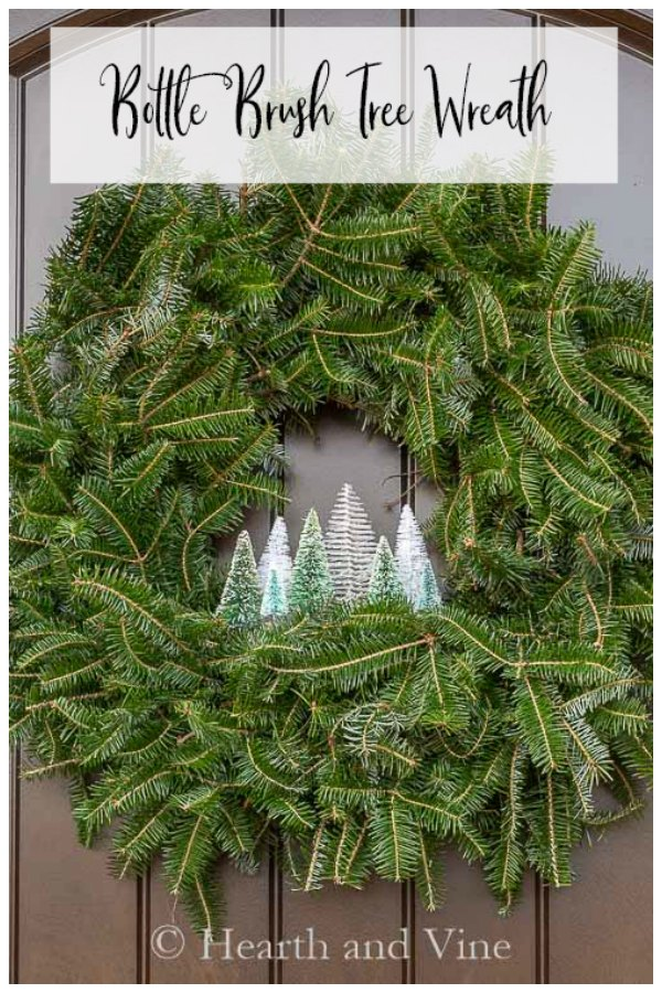 Evergreen wreath with little village of bottle brush tree inside.