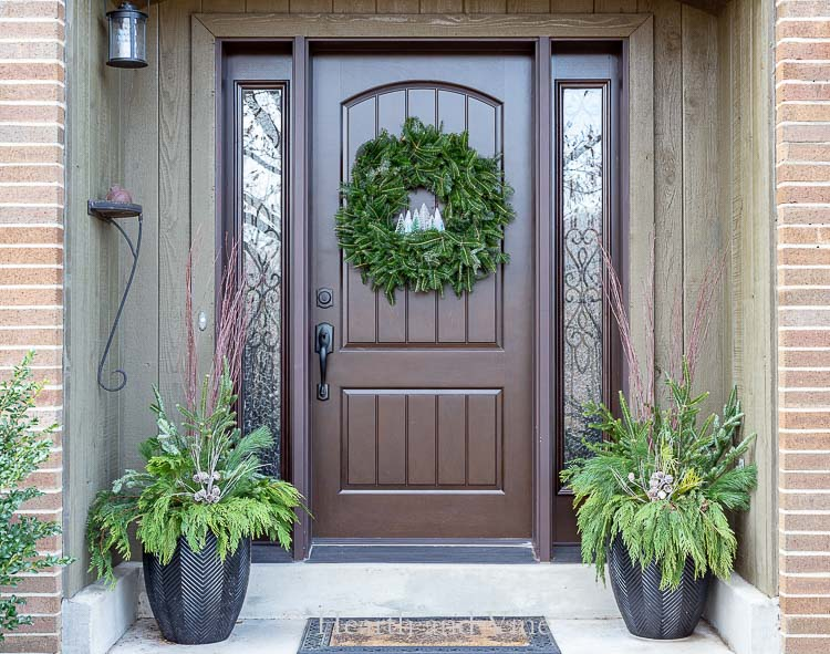 Front porch with bottle brush tree wreath on door and evergreen planters on sides