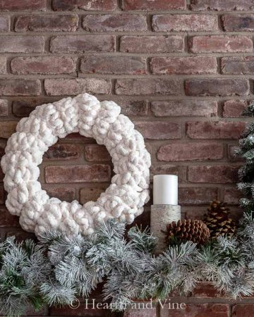 Decorated white Christmas mantel with a while wreath and flocked greenery
