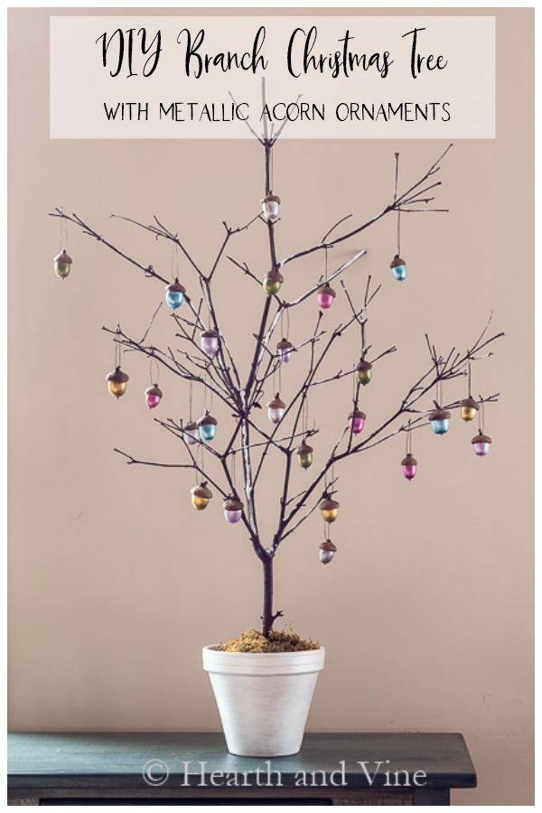 Christmas tree in pot from a branch with colorful acorn ornaments