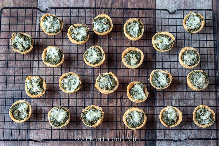 Cheesy spinach muffins cooking on rack