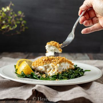 Fork of baked halibut with chickpea crumb topping.