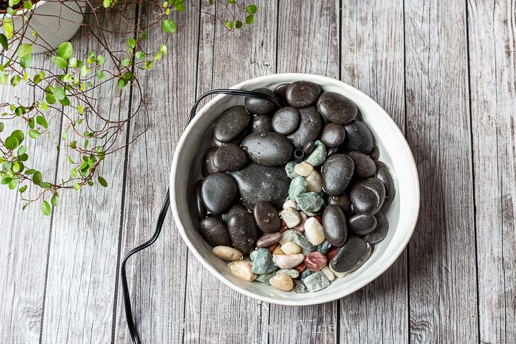 Small indoor water fountain with black stones and colored rocks