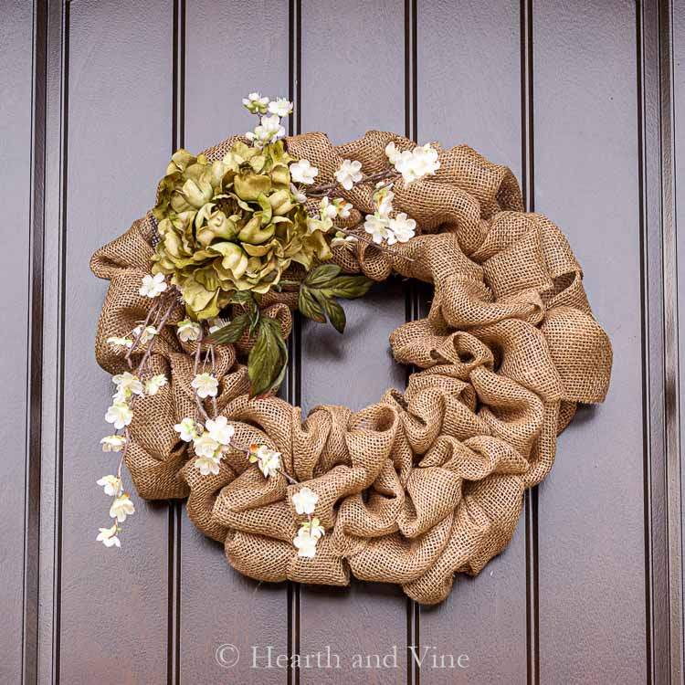 Burlap wreath with green and white flowers on front door.