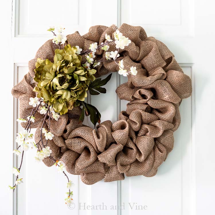 Burlap wreath with flowers on white door