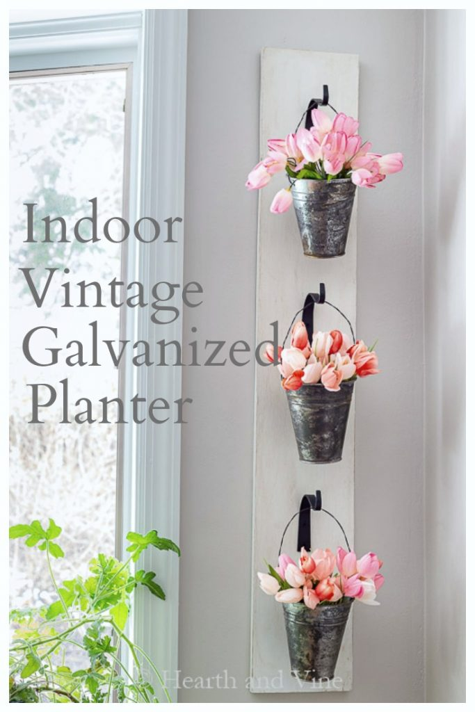 Hanging wall planter with galvanized pails filled with artificial tulips